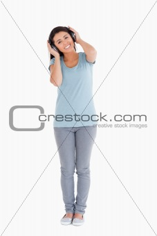 Beautiful woman using her headphones while standing