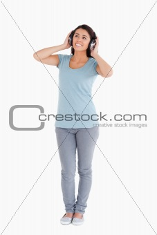 Attractive woman using her headphones while standing