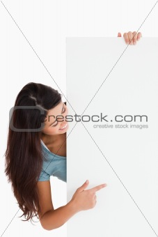 Attractive woman pointing at a board