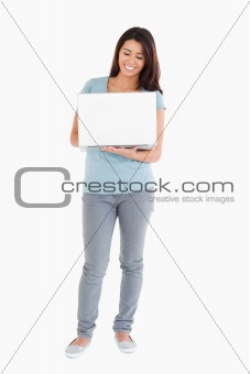 Beautiful woman holding a laptop while posing