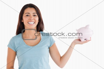 Beautiful female holding a piggy bank