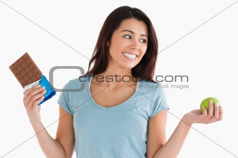 Attractive female holding a chocolate bar and an apple