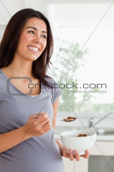 Attractive pregnant woman enjoying a bowl of cereal