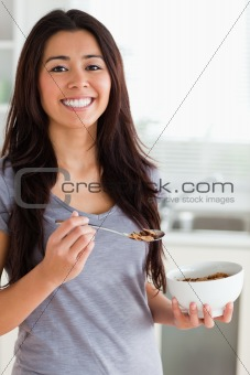 Gorgeous female enjoying a bowl of cereals while standing