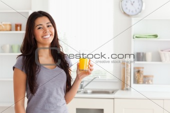 Attractive woman holding a glass of orange juice while standing