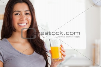 Good looking woman holding a glass of orange juice while standing