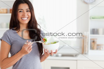 Beautiful woman enjoying a bowl of salad while standing