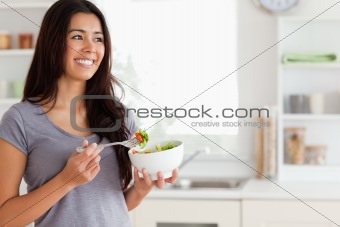 Attractive woman enjoying a bowl of salad while standing