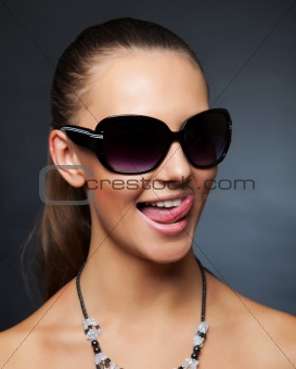 Girl with sunglasses showing her tongue