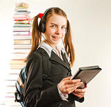 Teen girl with electronic book with a stack of printed books behind