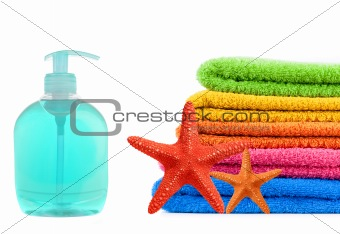 Blue soap bottle, stacked colorful towels and red seastars on a