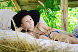boy in a cowboy hat is in the hayloft