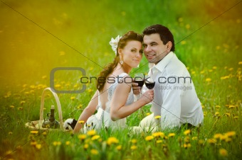 Bride and Groom drink a wine in the field of dandelion