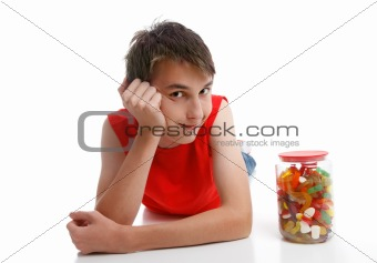 Boy beside an assortment of mixed confectionery