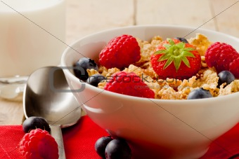 Corn flakes with berries on wooden table