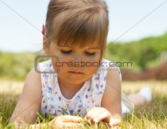 Little girl lying on grass in the park