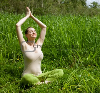 Beautiful young woman meditating in green grass