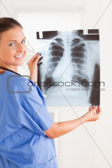 Charming doctor smiling at the camera holding a x-ray