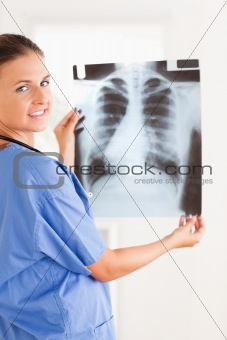 Charming doctor smiling into the camera holding a x-ray