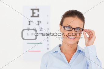 Good looking eye specialist wearing glasses looking into the camera