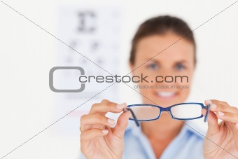 Portrait of a brunette eye specialist handing out glasses smiling into the camera
