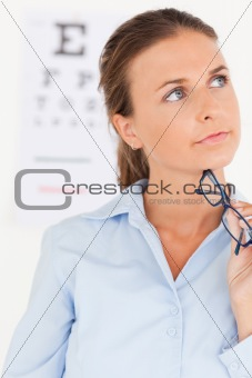 close up of a thinking eye specialist holding glasses