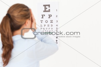 Beautiful brunette woman making an eye test