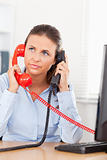 Businesswoman telephoning with two telephones