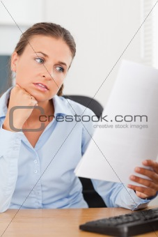 Charming brunette businesswoman looking at a paper