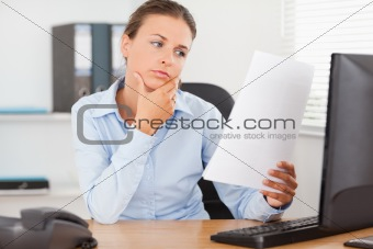 Charming businesswoman concentrating on a paper