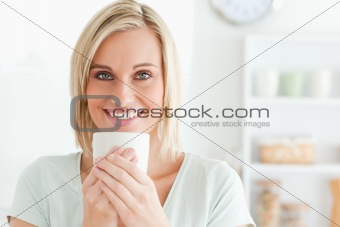Close up of a woman taking in smell of coffee looking into the c