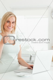 Charming woman with a cup of coffee and a laptop