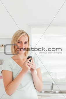 Cute woman with a mobile looking into the camera