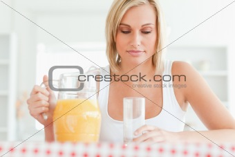 Close up of a woman sitting at a table with orange juice and gla