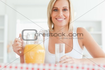 Close up of a woman sitting at a table with orange juice