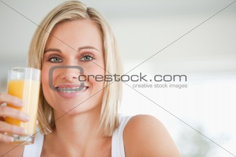 Close up of a smiling woman toasting with orange juice