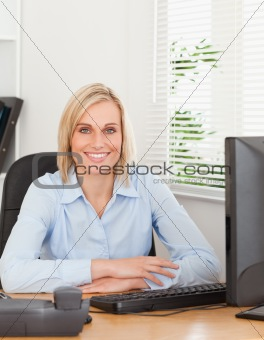 Smiling blonde woman sitting behind a desk