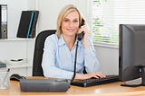 Smiling businesswoman on the phone looking into camera