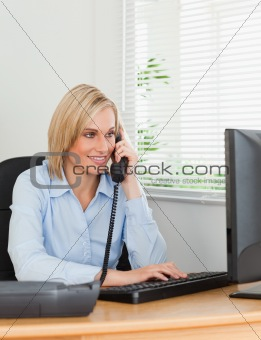 Smiling blonde businesswoman on the phone looking at her screen