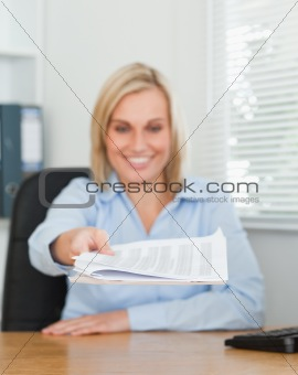 Smiling blonde businesswoman passing a paper looking at it