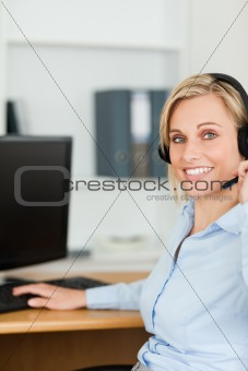 Close up of a smiling blonde businesswoman with headset working