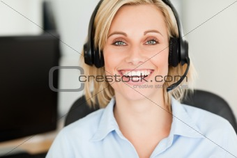 Close up of a blonde woman wearing headset looking into camera