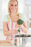 Close up of a woman cooking broccoli looks into the camera