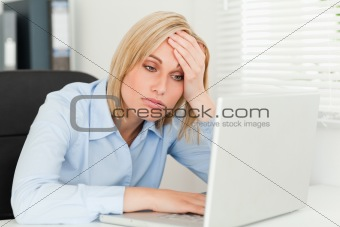 Blonde business woman touching her forehead being tired