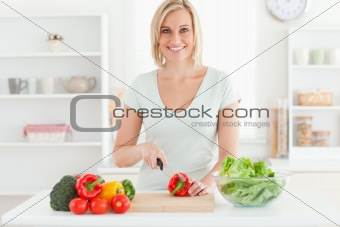 Young woman cutting vegetables smiles into camera