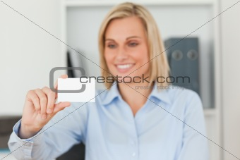 Blonde businesswoman holding a card