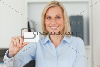 Blonde businesswoman holding a card looks itno camera