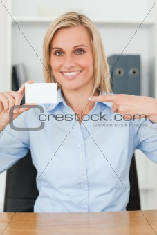 Smiling blonde businesswoman pointing at a card