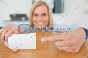 Blonde businesswoman pointing at a card crouching behind her desk