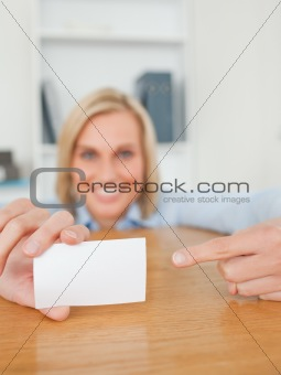 Blonde smiling businesswoman pointing at a card crouching